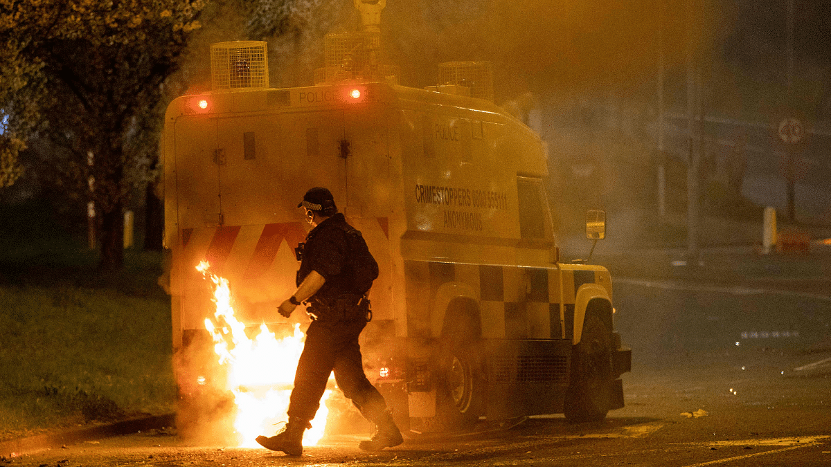A police officer walks behind a police vehicle with flames leaping up the rear after violence broke out in Newtownabbey, north of Belfast, in Northern Ireland on April 3, 2021