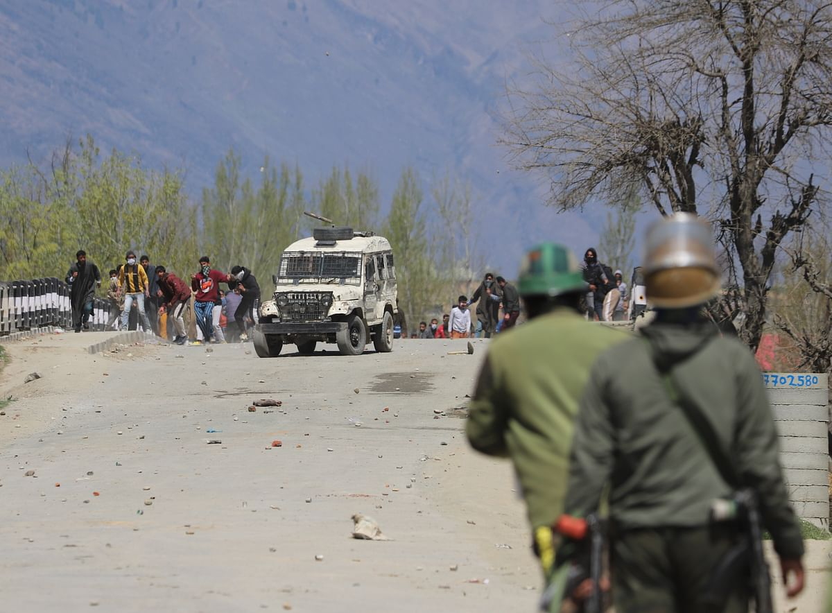 Policemen stand in position as Kashmiri protesters throw stones towards the government forces during the clashes near the site of encounter in Pulwama district of South Kashmir.