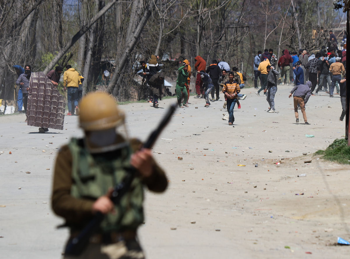 Kashmiri protesters throw stones towards the government forces during the clashes near the site of the gunfight in the Pulwama district of South Kashmir.