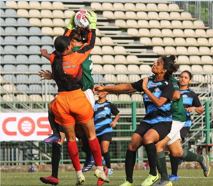 India Rush FC goalkeeper Shruti Nair make a good overhead collection to foil a Kenkre FC striker's attempt
