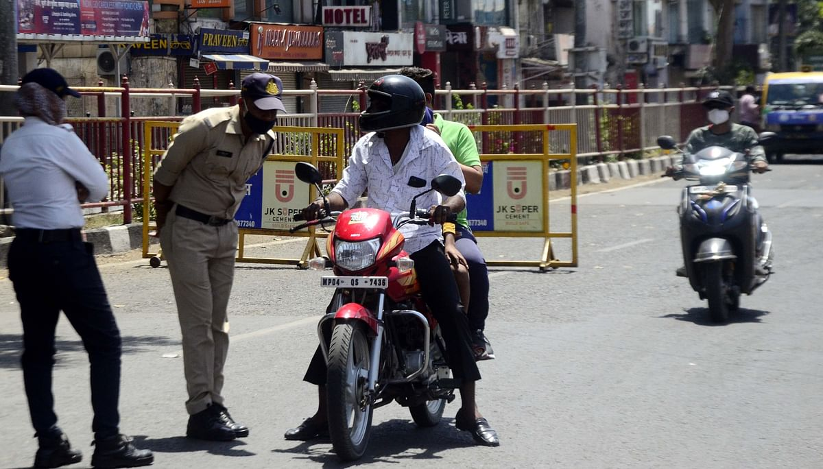Police intercept people when they were spotted moving on the road during the lockdown at Roshanpura Square on Sunday.