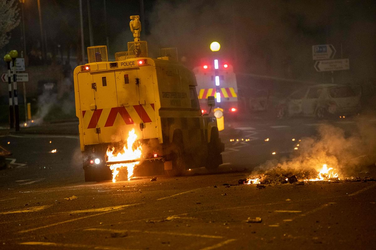 Flames are seen at the rear of a police vehicle after violence broke out in Newtownabbey, north of Belfast, in Northern Ireland on April 3, 2021