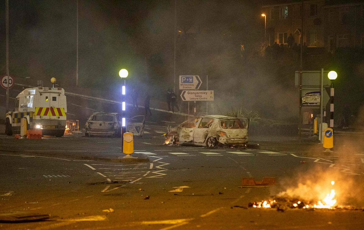A burnt out car and flames are seen at the scene of violence in Newtownabbey, north of Belfast, in Northern Ireland on April 3, 2021.