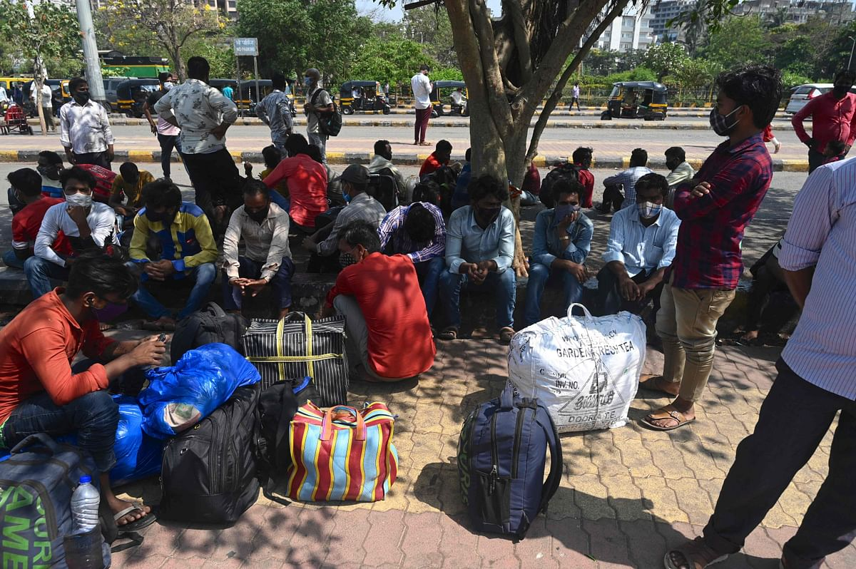 A group of migrant workers wait under the shade of a tree outside Lokmanya Tilak Terminus railway complex to catch a train back home ahead of the harvest season amidst rising Covid-19 coronavirus cases in Mumbai on April 6, 2021.
