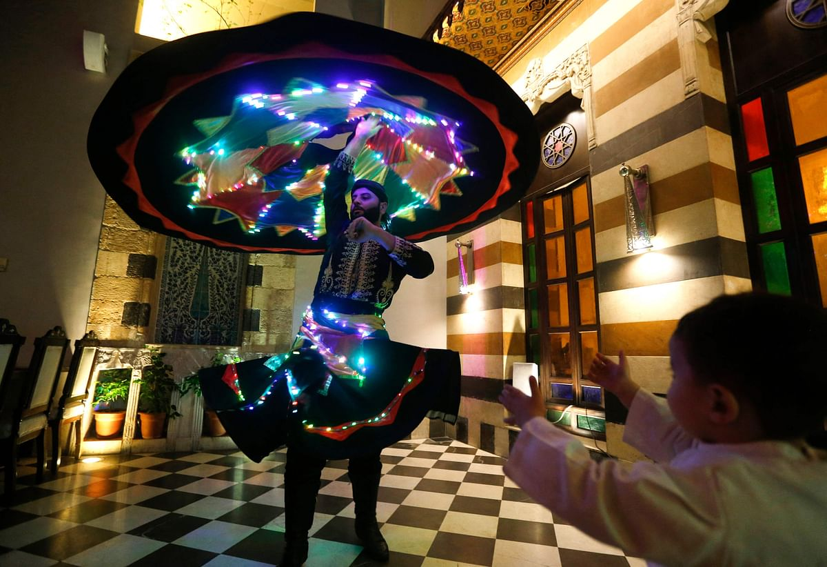 Sufi Dervish dancer Muayad al-Kharrat, 28, dances with his lit dress at a restaurant in the Shahgur district of the old city of Syrias capital Damascus on May 5, 2021.