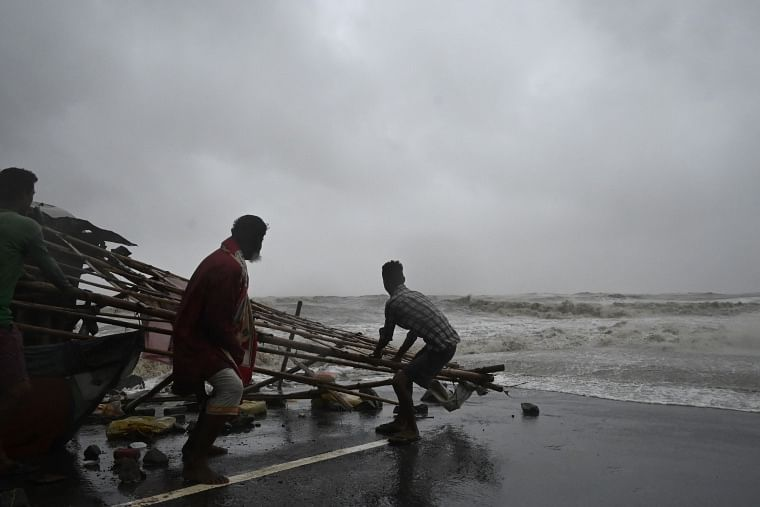 Residents shift structures of makeshifts stalls as water reaches a road at a beachfront area while strong winds batter Balasore district