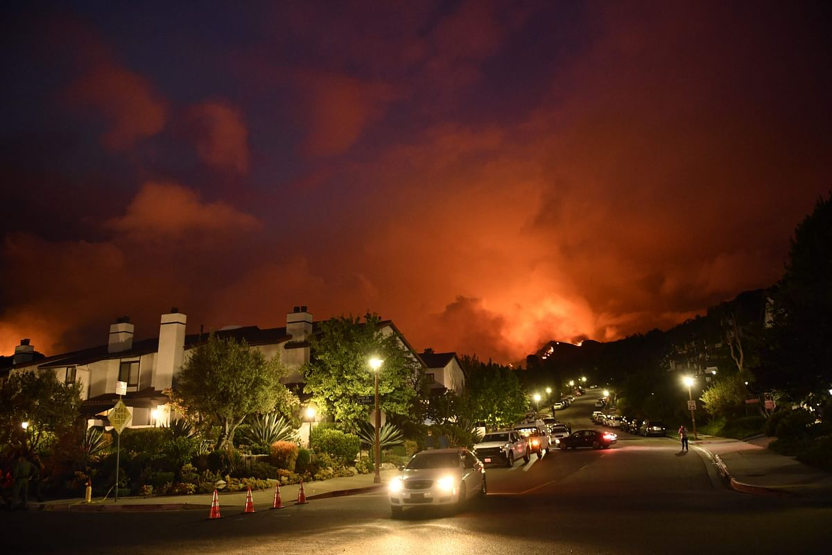 Flames from the Palisades Fire glow in the distance in Topanga, northwest of Los Angeles, May 15, 2021.