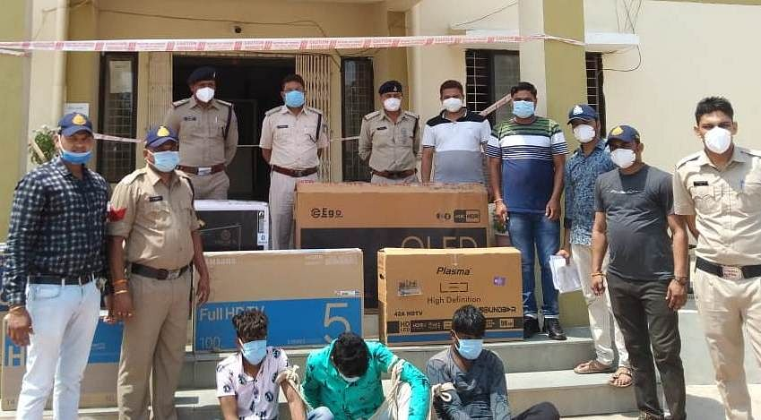 Police with 3 accused outside Kukshi police station on Saturday. Seized TV sets are also seen