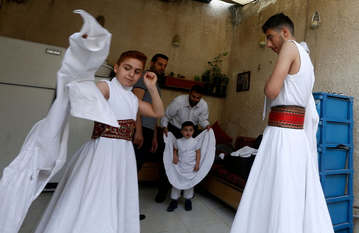 Sufi Dervish dancers of the Kharrat family don their costumes at their home in the Shahgur district of the old city of Syrias capital Damascus on May 6, 2021.