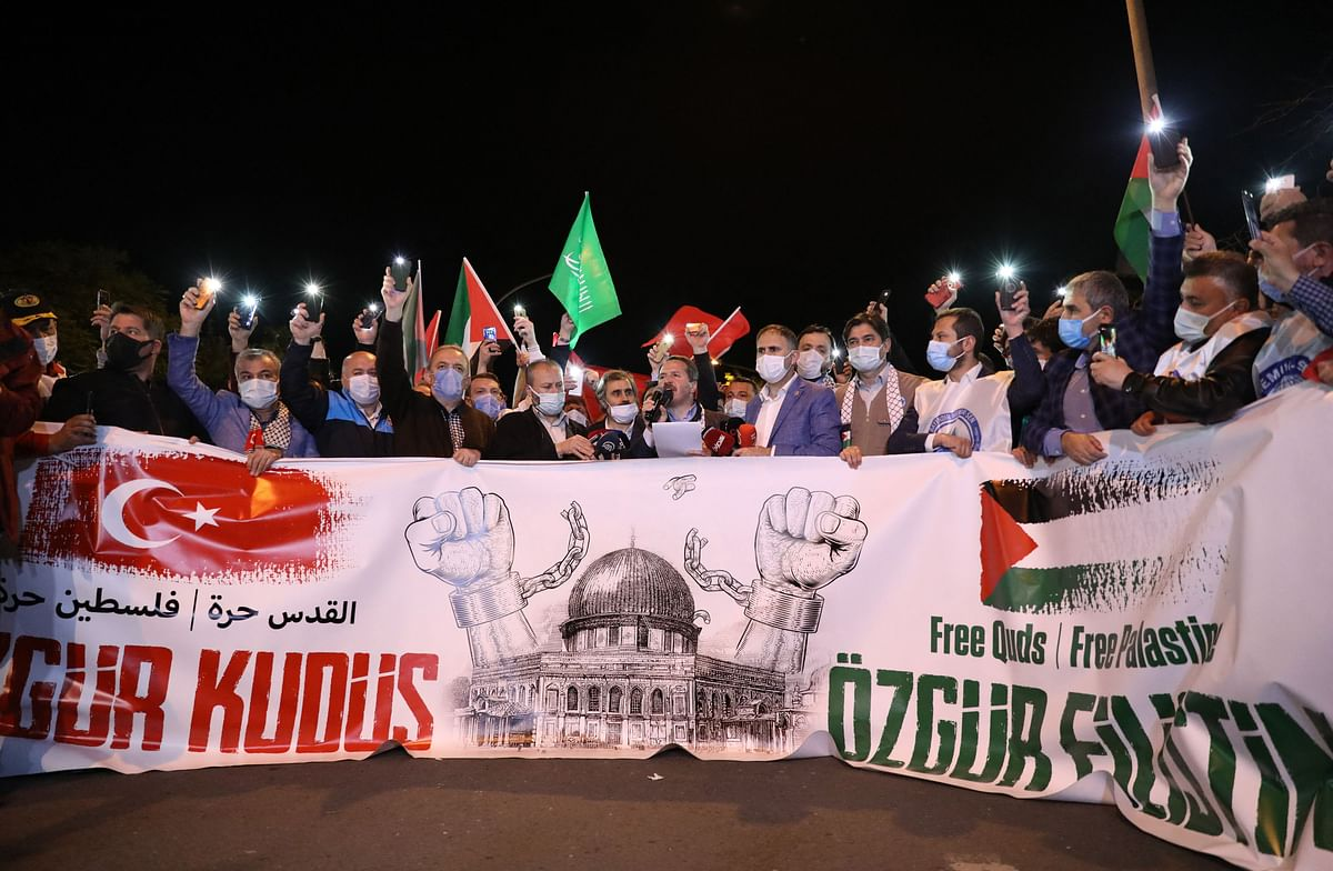Protesters hold Palestine and Turkish national flags and chant slogans during a demonstration outside the Israel Consulate in Istanbul, late on May 10, 2021