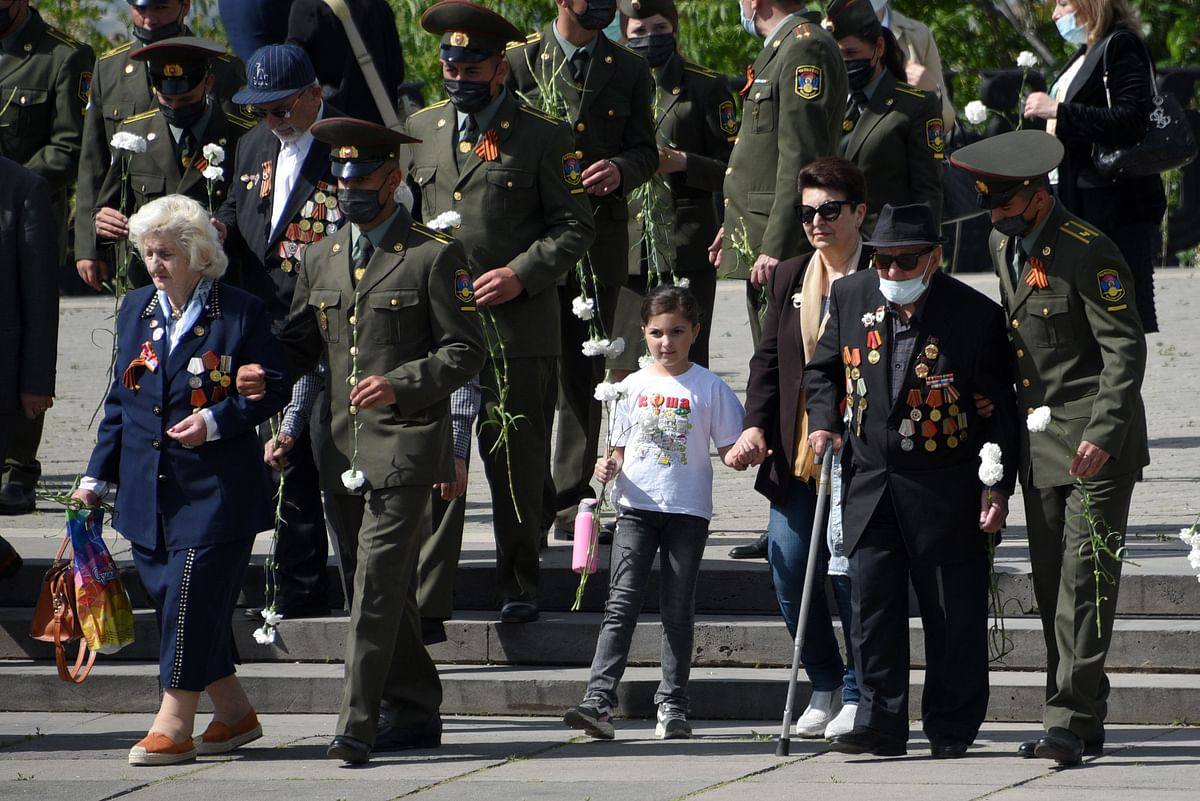 Veterans walk to lay flowers at the Mother Armenia monument in the Victory Park during the Victory Day celebrations in Yerevan on May 9, 2021.