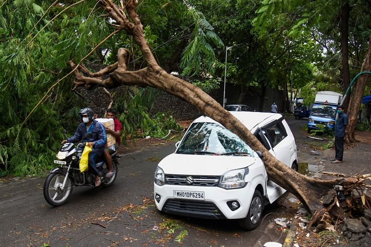 A motorist rides past a damaged car at a street in Mumbai on May 18, 2021, after Cyclone Tauktae hit the west coast of India with powerful winds and driving rain, leaving at least 24 people dead and almost 100 missing.