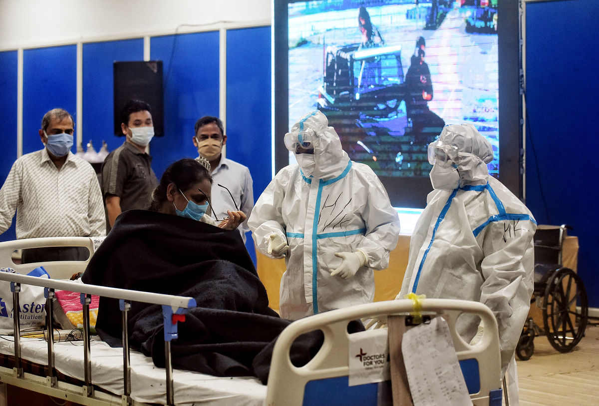 Health workers in PPE kit attend COVID patient at CWG COVID Care Centre, in New Delhi on Tuesday.
