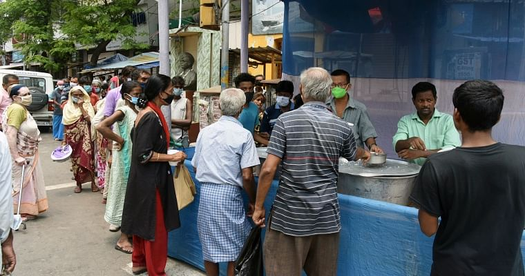 People stand in a queue to get free food during the lockdown in Kolkata on Sunday.