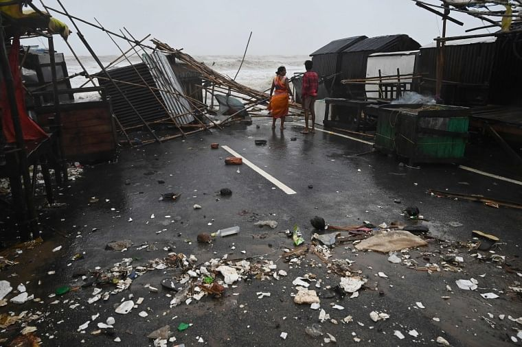 A resident walks amidst debris near stalls in a beachfront area while strong winds batter Balasore district