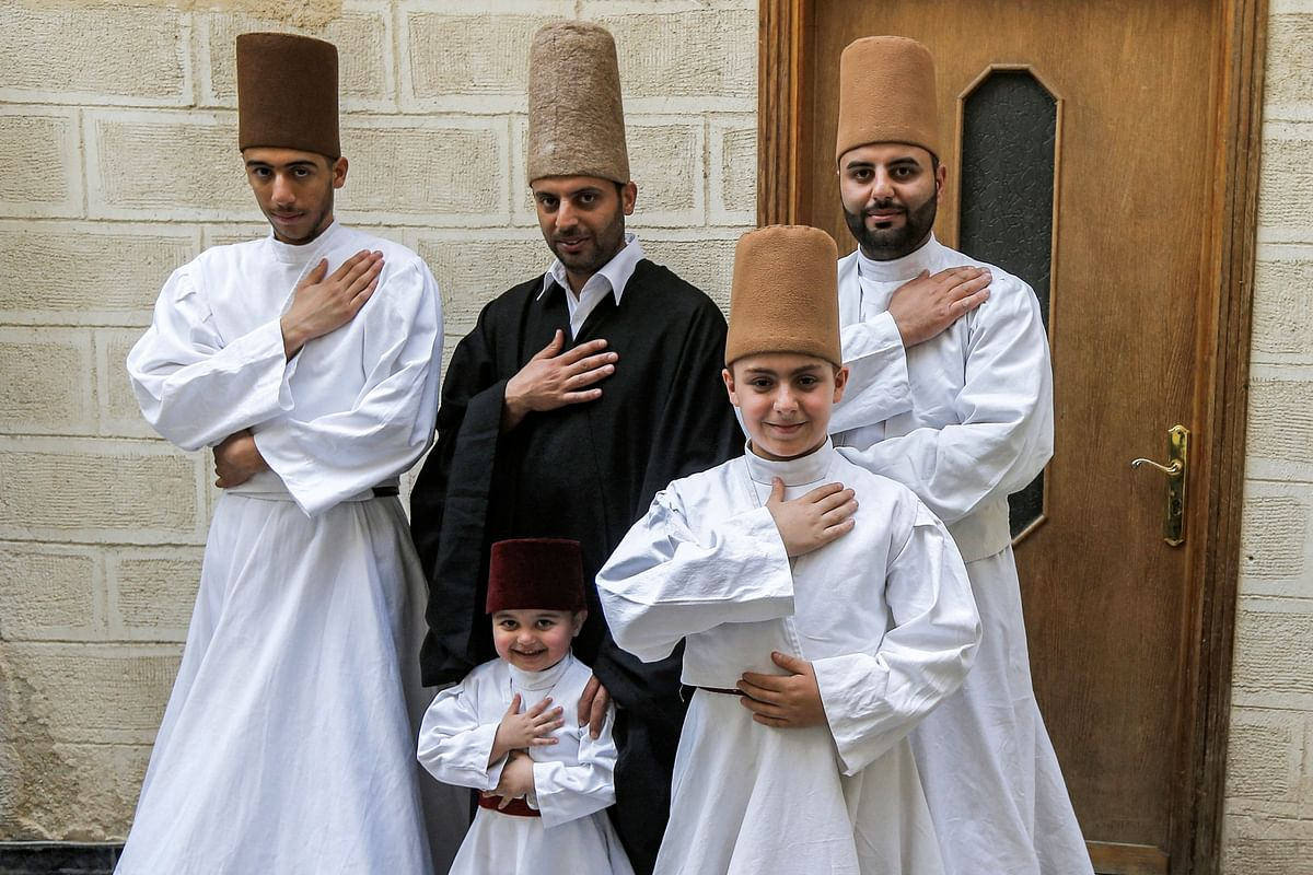 Sufi Dervish dancer Mahmoud al-Kharrat (C top), his brother Muayad (R behind), Muayads son Anas (C below) and other members of the Kharrat family pose for a picture in costume at their home in the Shahgur district of the old city of Syrias capital Damascus on May 6, 2021