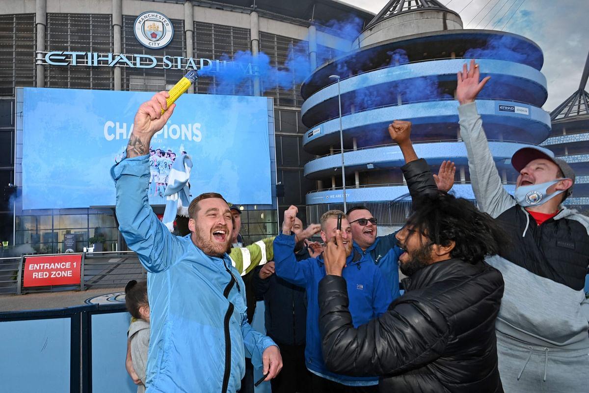 Manchester City fans celebrate outside the Etihad Stadium