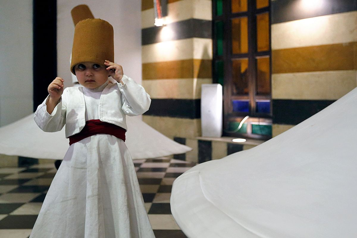 Three-year-old Sufi Dervish dancer Anas al-Kharrat dances with his family members at a restaurant in the Shahgur district of the old city of Syrias capital Damascus on May 5, 2021.