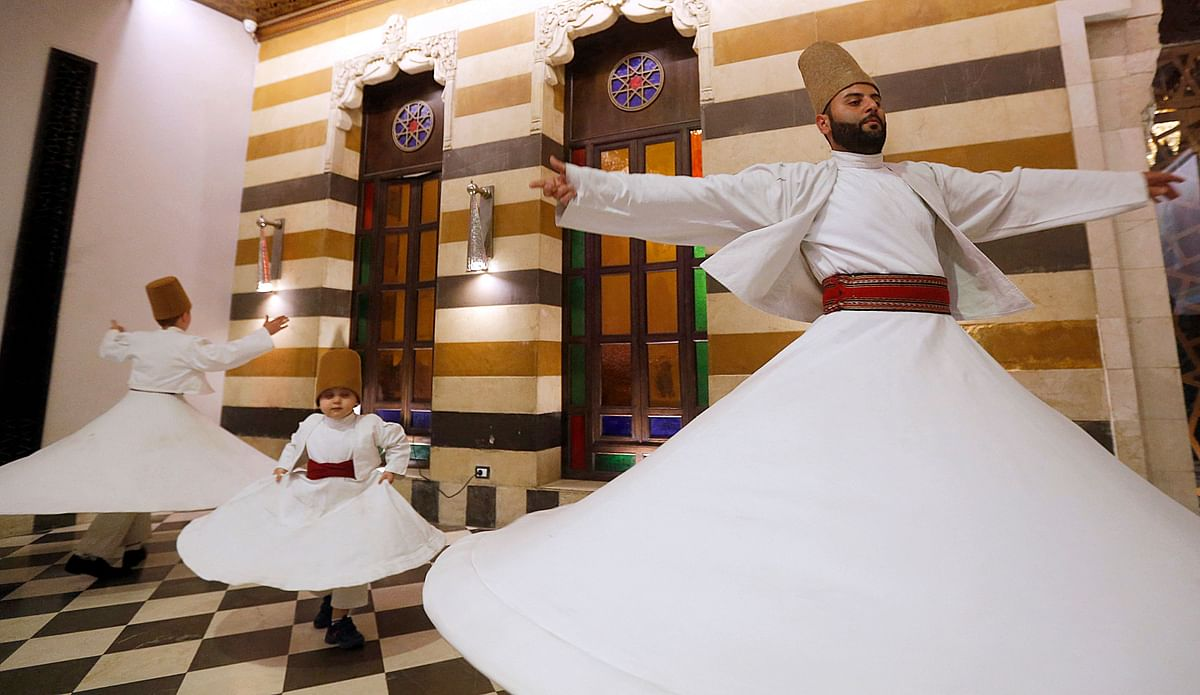 (L to R) Sufi Dervish dancers Yasser, Anas, and Muayad al-Kharrat, members of the Kharrat family, dance at a restaurant in the Shahgur district of the old city of Syrias capital Damascus on May 5, 2021.