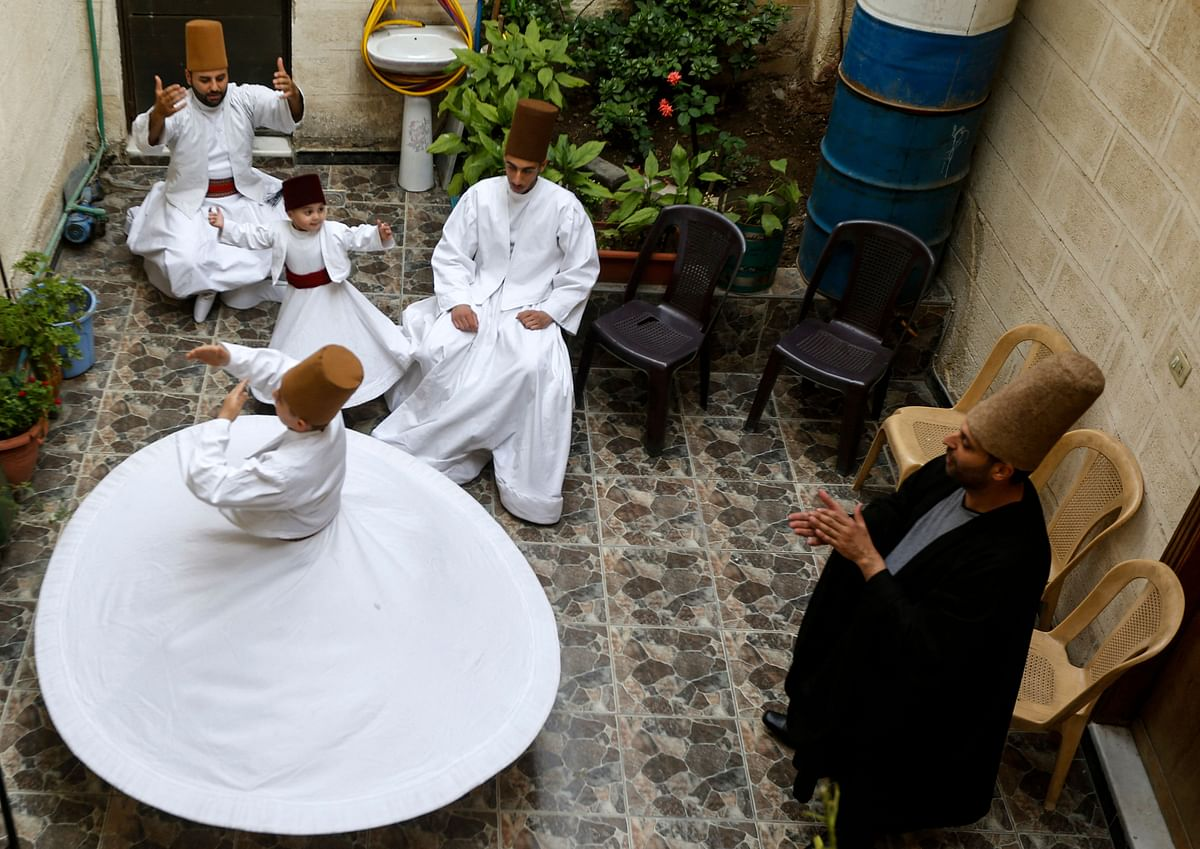Sufi Dervish dancer Mahmoud al-Kharrat (R), 34, applauds other members of his family as they dance at a courtyard in their house in the Shahgur district of the old city of Syrias capital Damascus on May 6, 2021.
