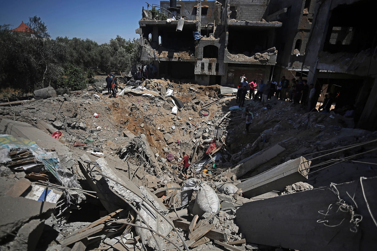 Palestinians inspect the damage of a destroyed house that was hit by an Israeli airstrike in the town of Khan Younis, southern Gaza Strip, Wednesday
