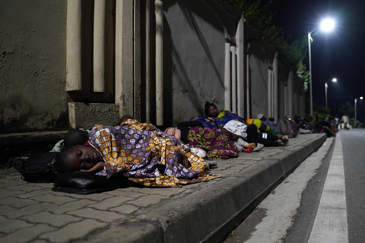 Congolese fleeing from Goma, Democratic Republic of Congo (DRC), sleep with their belongings on a street after the Nyiragongo volcano erupted near the border in Gisenyi, Rwanda, on May 23, 2021