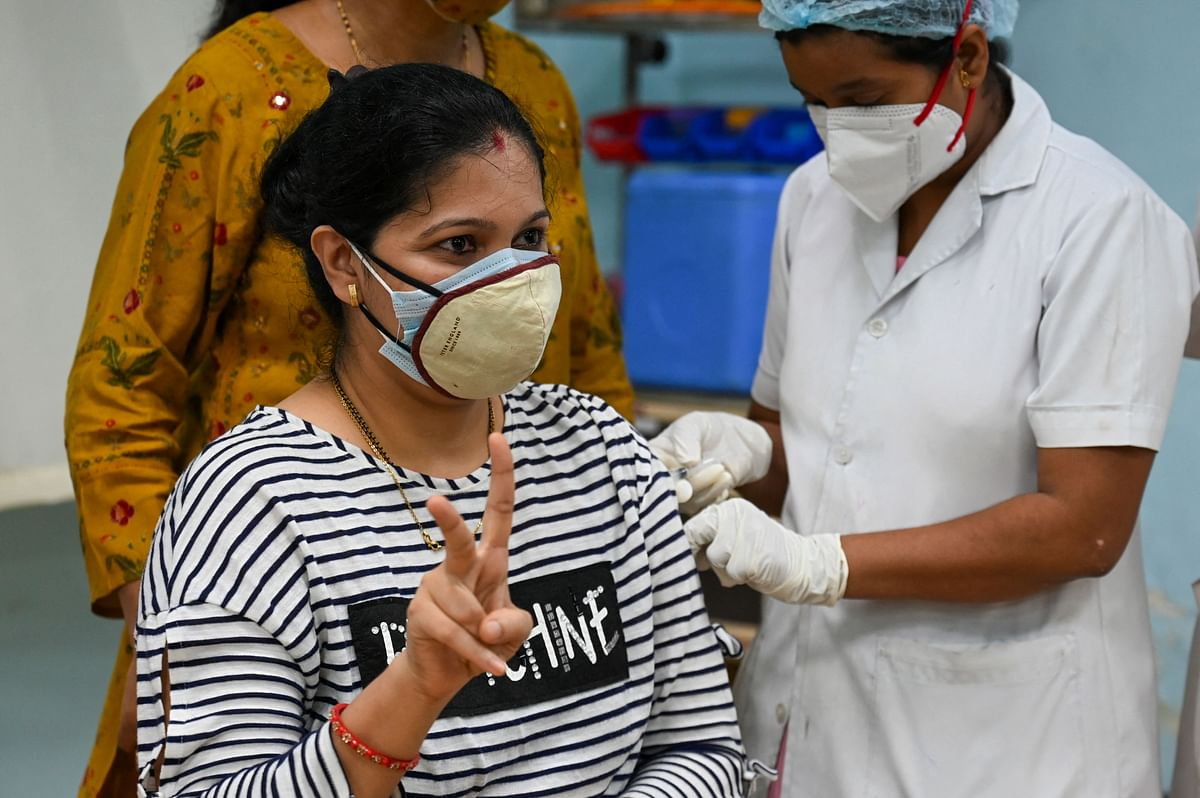 A woman flashes victory sign as she gets inoculated with a dose of Covishield vaccine against the Covid-19 coronavirus at a vaccination centre of the Rajawadi Hospital in Mumbai.