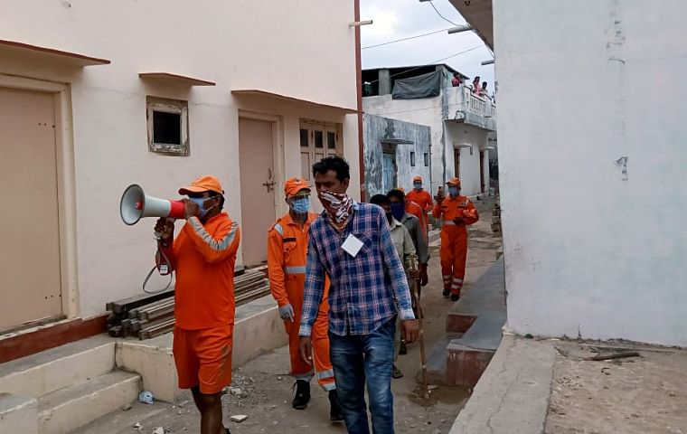 NDRF personnel alert people to stay away from the sea ahead of the landfall of cyclone 'Tauktae' on Monday