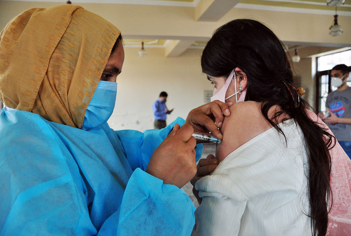 Jammu and Kashmir, May-24 (ANI): A Kashmiri woman receives a shot of a vaccine against COVID-19 as vaccinations drive resumes in Kashmir valley with the fresh stock of Covid-19 vaccines, at a local Vaccination center at Chanapora, in Srinagar on Monday.