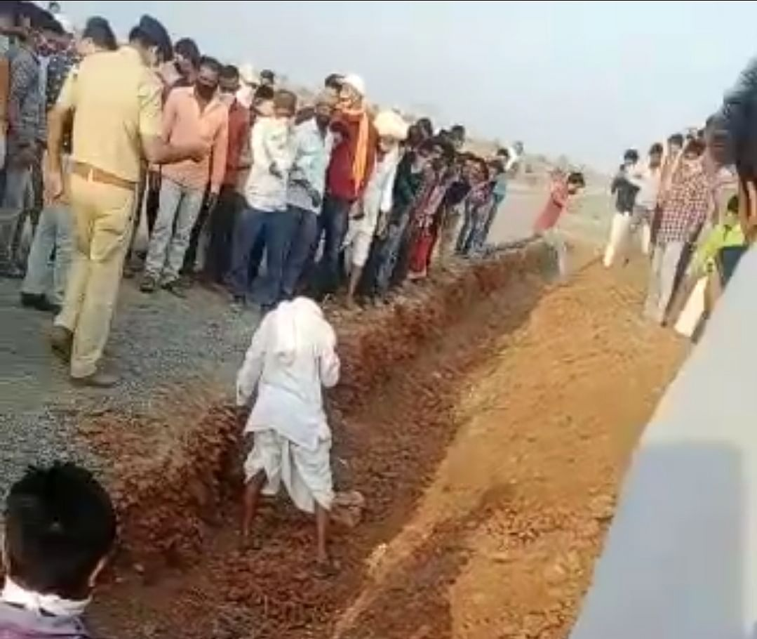 Police and villagers exhuming the body