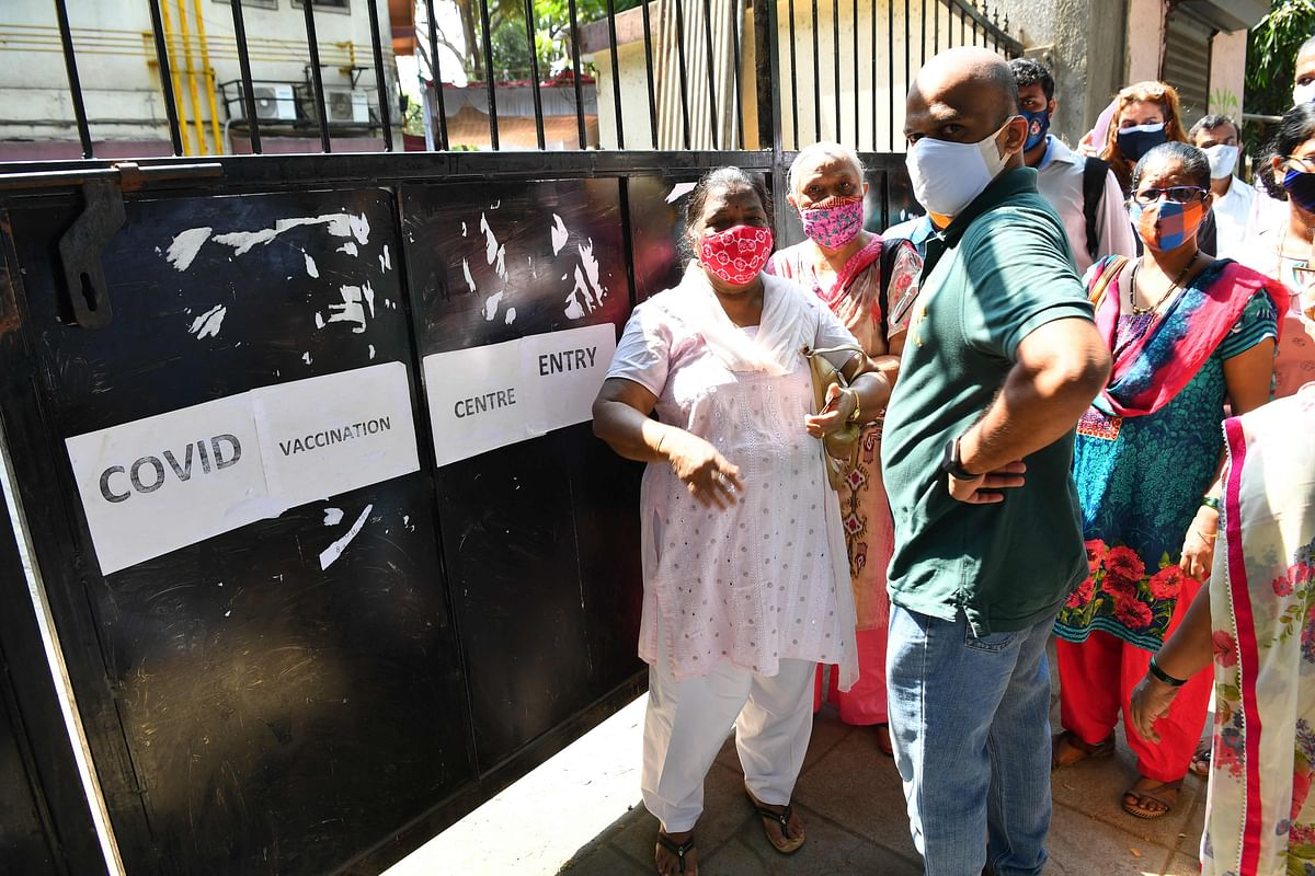 People stand outside a closed vaccination centre due stock shortages of Covid-19 coronavirus vaccines in Mumbai on May 6, 2021.