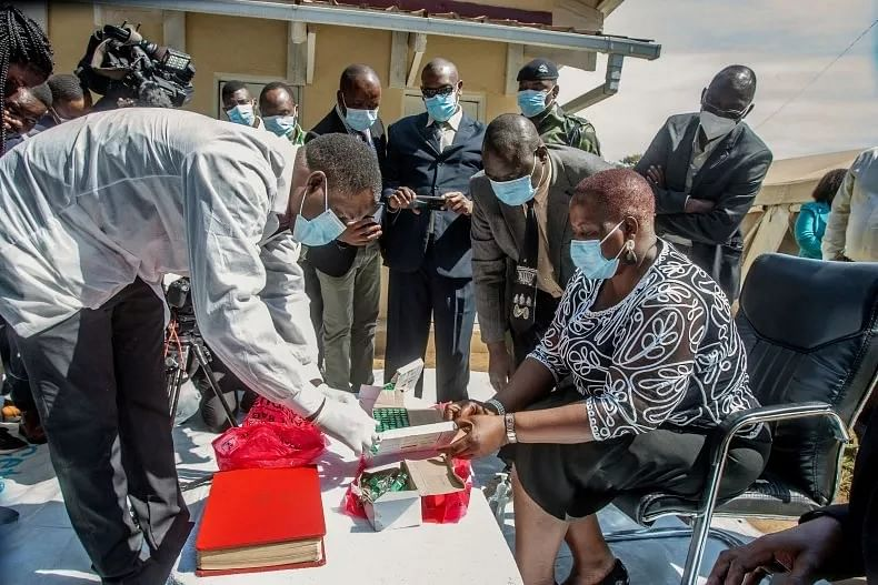 A pharmaceutical expert (L) opens a pack of expired COVID-19 Astra Zeneca vaccines to show to Malawi's Health Minister Khumbize Kandodo Chiponda (R) before they are destroyed in a furnace at a pharmaceutical incinerator at Kamuzu Central Hospital in Lilongwe on May 19, 2021