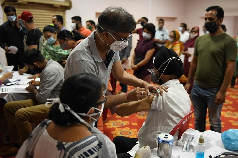 A health worker inoculates a man with a dose of the Covaxin Covid-19 coronavirus vaccine at a vaccination camp organised at a temple in Amritsar