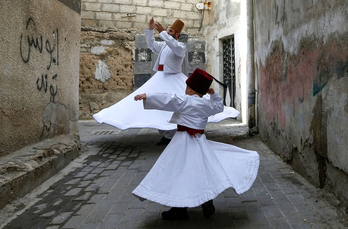 Sufi Dervish dancer Muayad al-Kharrat (behind), 28, dances with his three-year-old son Anas (front) by their home in the Shahgur district of the old city of Syrias capital Damascus on May 6, 2021.