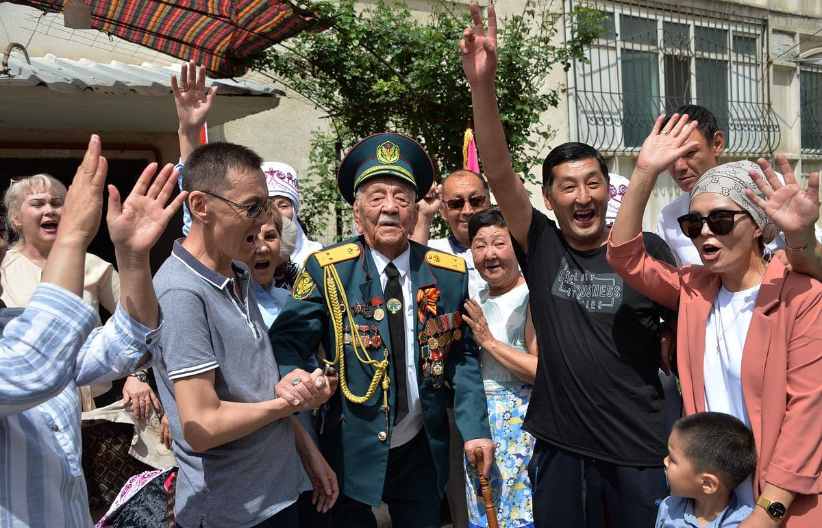 World War Two veteran Asek Urmanbetov, 98, receives congratulations from Kyrgyz servicemen during the Victory Day celebrations in Bishkek, Kyrgyzstan on May 9, 2021.