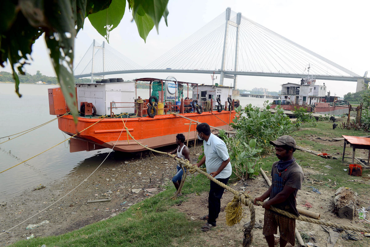 West Bengal, May 23 (ANI): A barge vessel being pulled out from the water as a precautionary measure against approaching Cyclone Yaas, near Vidyasagar Bridge in Kolkata on Sunday.