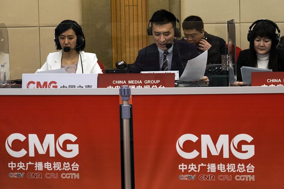 """China's state broadcaster CCTV news broadcasters read news at a media centre during a news conference on the eve of the annual legislature opening session in Beijing on March 4, 2021. Israel's Embassy in China is protesting what it describes as """"blatant anti-Semitism"""" on a program run by the overseas channel of state broadcaster CCTV discussing the ongoing violenc Gaza and elsewhere."""