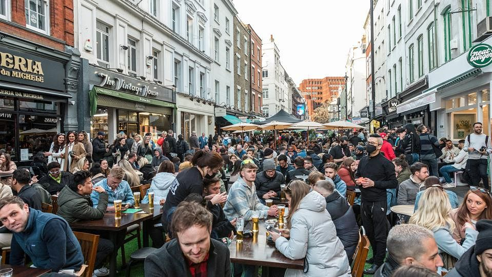 Crowds of people in restaurants and bars in Soho, London, where outdoor seating is allowed following a lift in COVID restrictions.