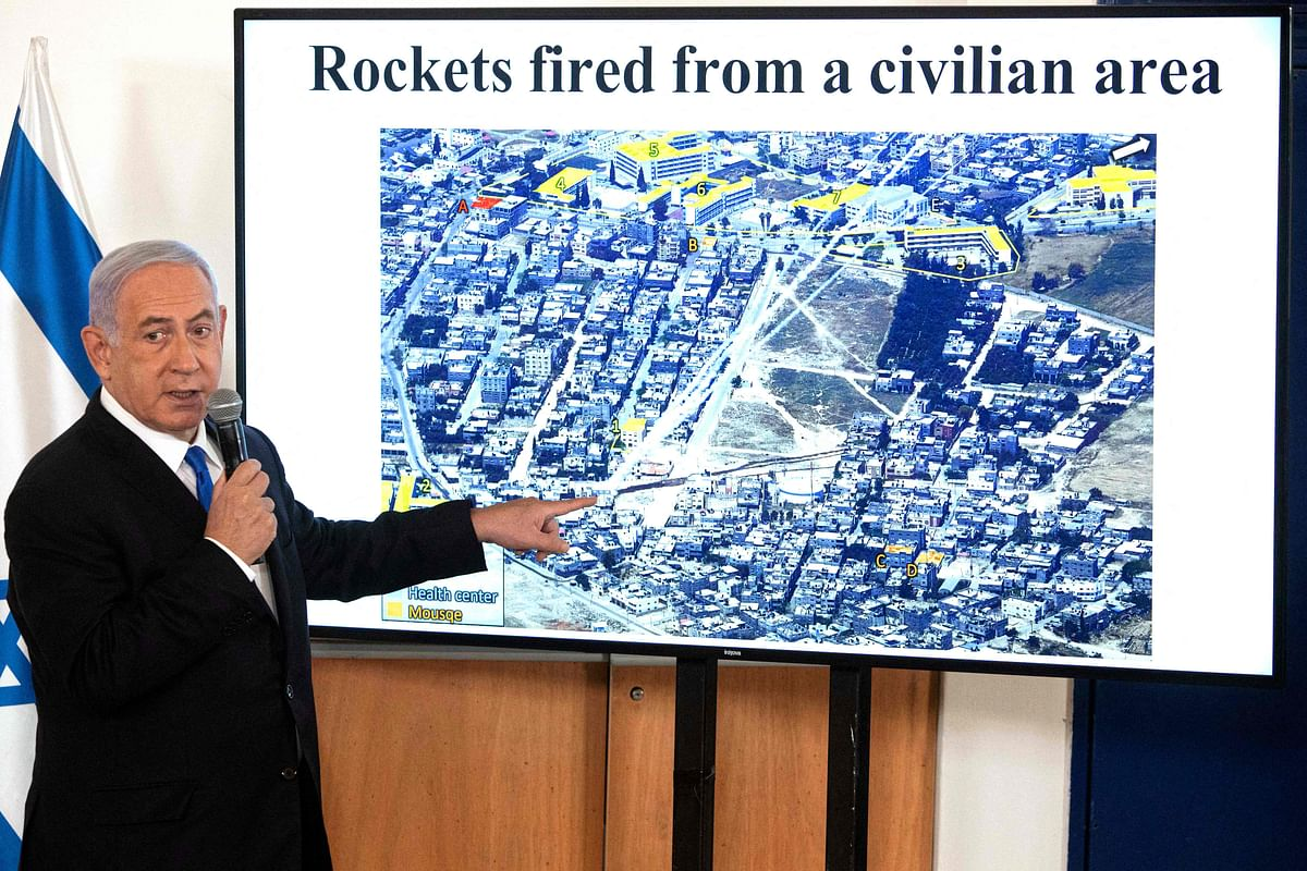 """Israeli PM Benjamin Netanyahu gestures as he shows a slideshow during a briefing to ambassadors to Israel at the Hakirya military base in Tel Aviv, Israel on Wednesday. Israel is studying whether conditions are right to stop bombing Palestinian militants in Gaza but is preparing for """"more days"""" of strikes if necessary, an Israeli military source said."""