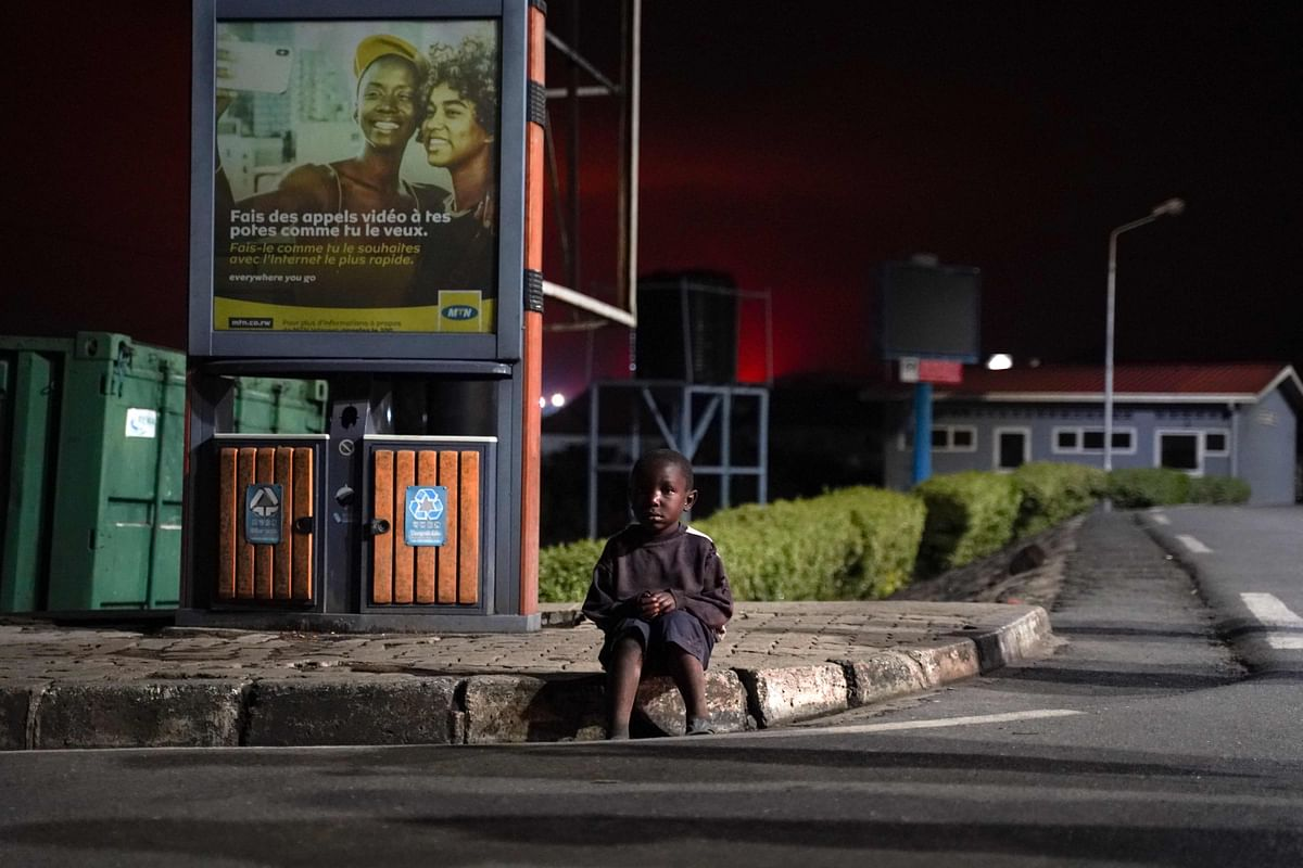 """A lost child sits on a curb as Congolese people flee from Goma after the Nyiragongo volcano erupted, at the border point known as """"Petite Barriere"""" in Gisenyi, Rwanda, on May 23, 2021."""