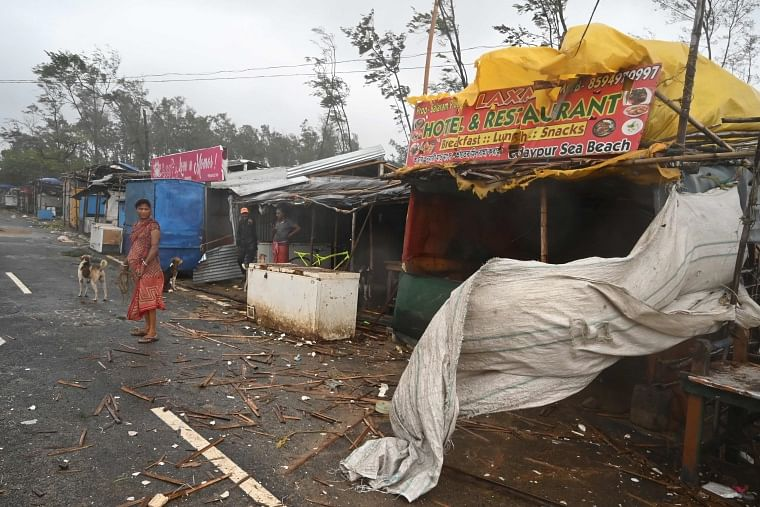 Residents stand near stalls along a road amidst debris while strong winds batter Balasore district