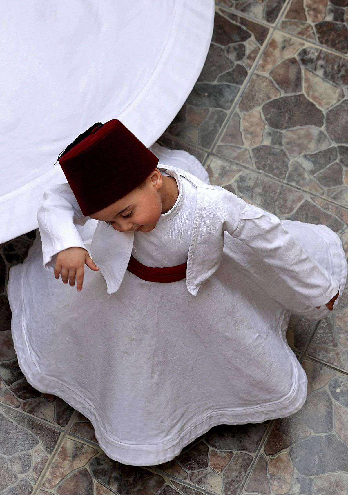 Three-year-old Sufi Dervish dancer Anas al-Kharrat dances at his home in the Shahgur district of the old city of Syrias capital Damascus on May 6, 2021.