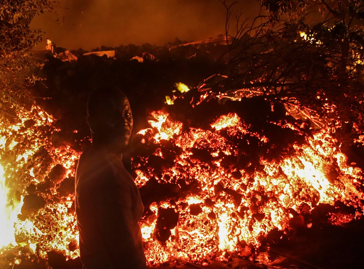 A person stands in front of lava from the eruption of Mount Nyiragongo, in Buhene, on the outskirts of Goma, Congo in the early hours of Sunday, May 23, 2021.
