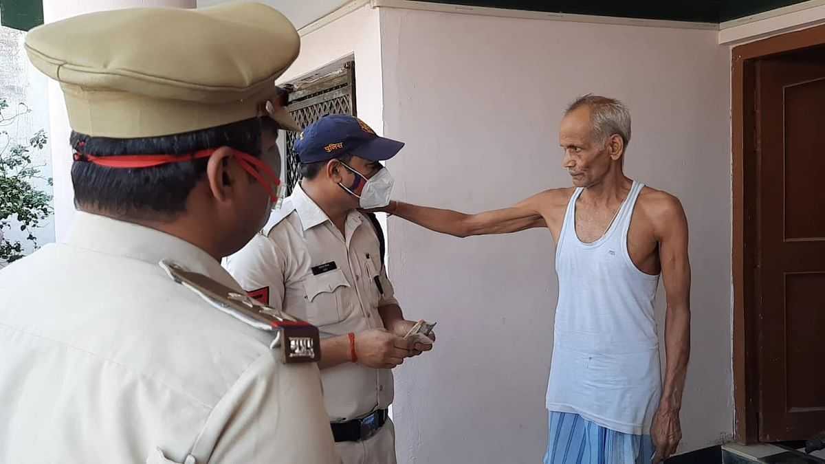 A retired personnel blessing police men after receiving medicines at his house in Satna town on Saturday