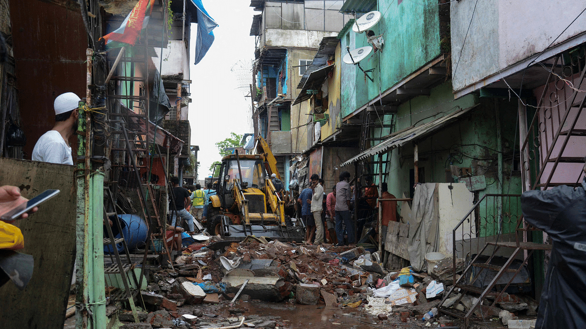 Civil authority and rescue personnel search for survivors in the debris of a building that collapsed following heavy monsoon rains, in Mumbai on June 10, 2021.