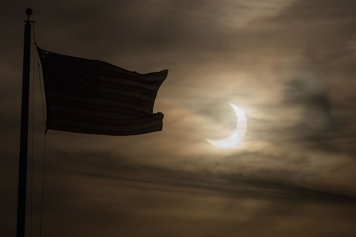 n eclipsed sun rises next to a flag on June 10, 2021 in Scituate, Massachusetts.