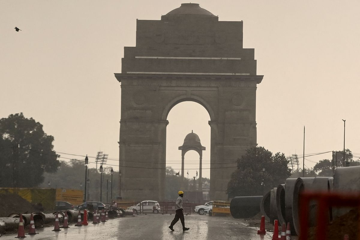 A construction worker walk near India Gate during a monsoon rainfall in New Delhi on June 17, 2021.