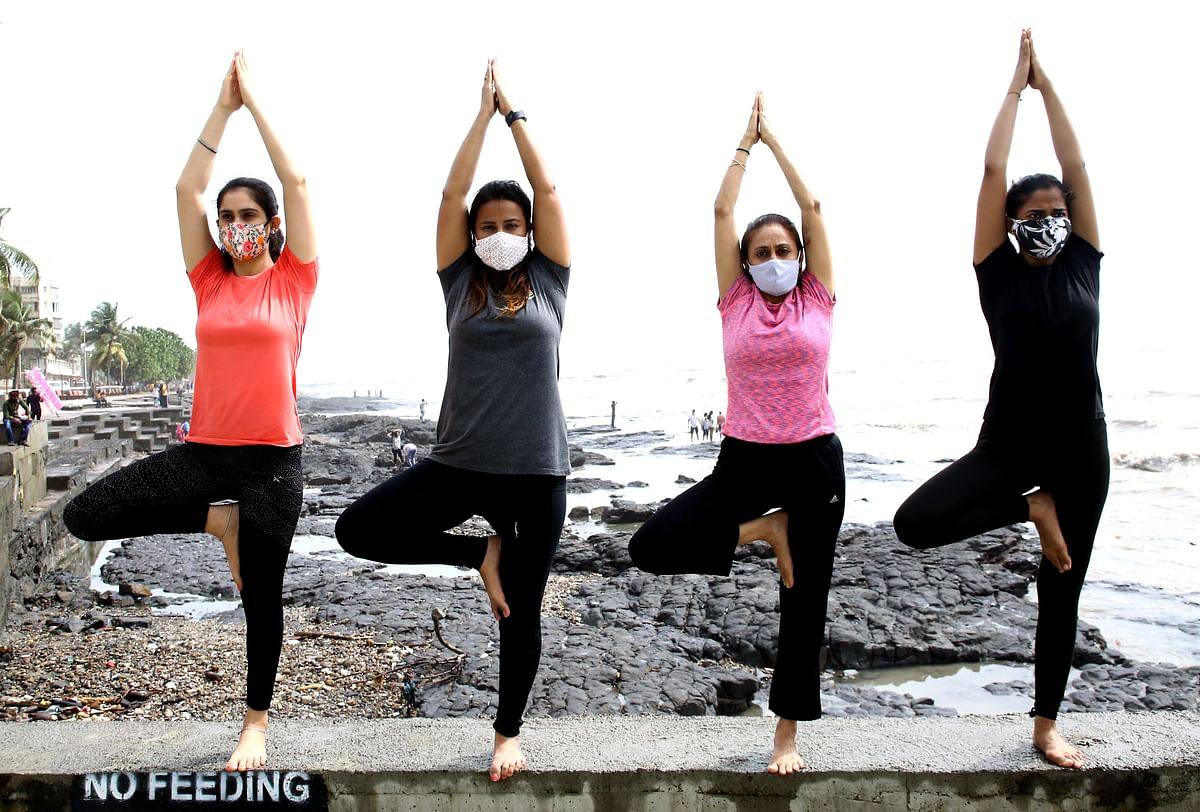 A group of girls performs yoga, on the occasion of the 7th International Yoga Day, at Bandra Bandstand, in Mumbai on Monday.
