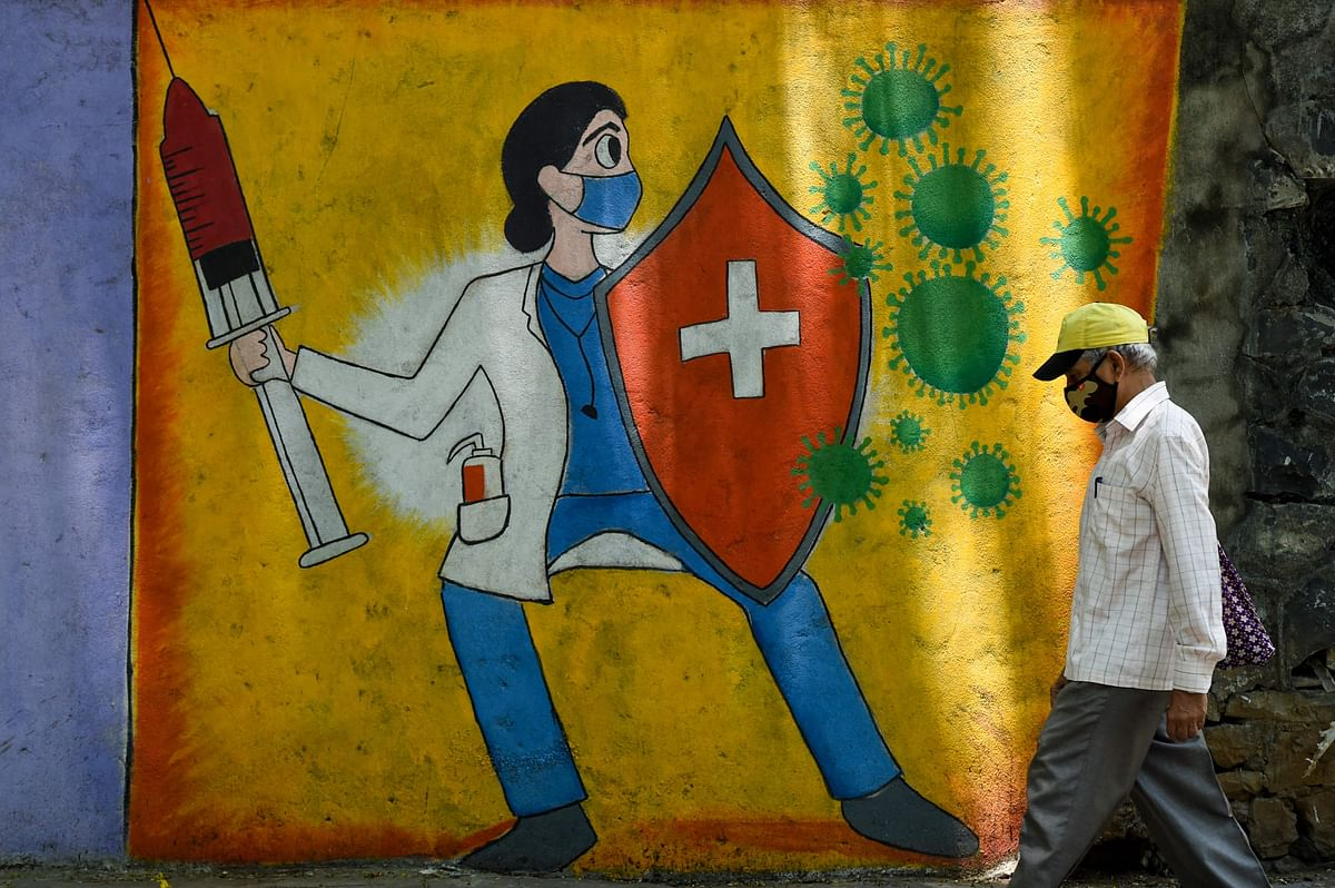 A resident walks past a wall mural depicting a health worker wearing a facemask while holding a vaccine and a shield to spread awareness about the Covid-19 coronavirus, in Mumbai on June 30, 2021.