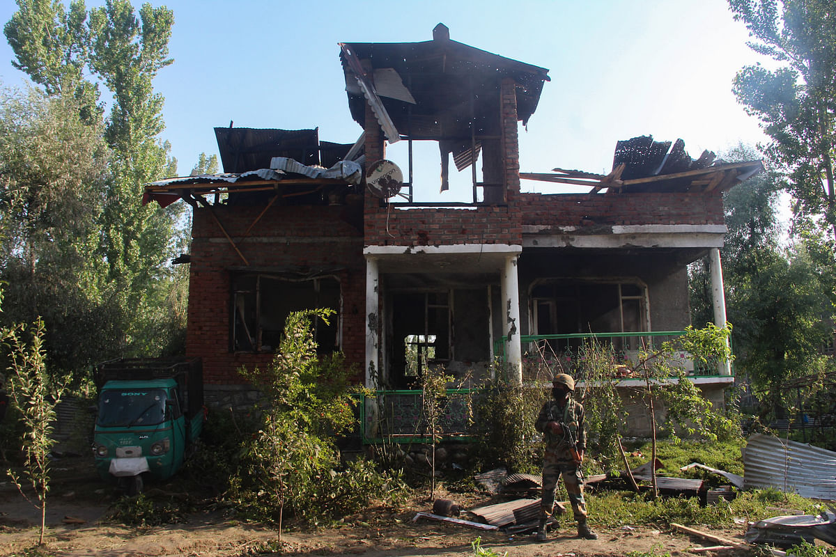 A soldier stands outside the damaged house where a gun-battle took place between suspected militants and government forces in the Maloora locality on the outskirts of Srinagar in Jammu & Kashmir.
